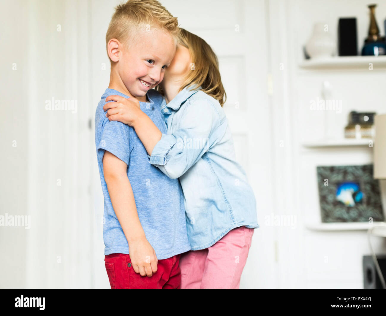 Little girl (4-5) whispering into brother's (4-5) ear - Stock Image