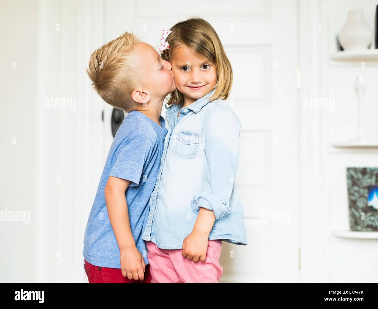 Little boy (4-5) kissing sister (4-5) - Stock Image