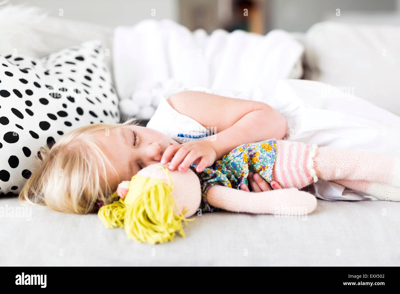Girl (2-3) napping on sofa - Stock Image