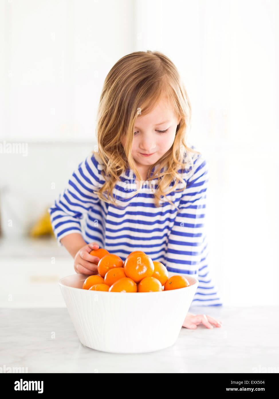 Girl (4-5) looking at oranges, smiling - Stock Image
