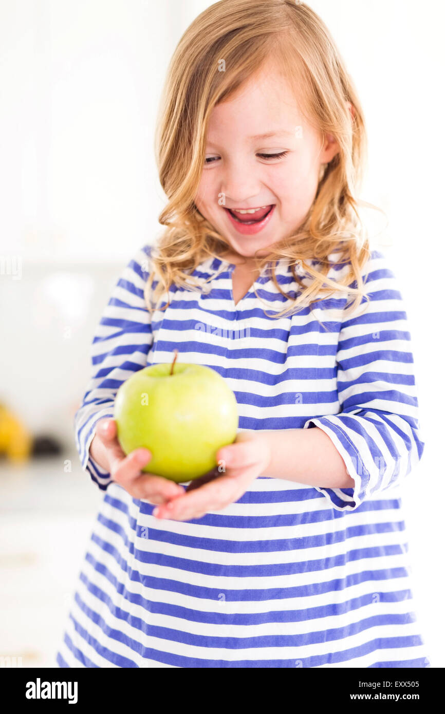 Girl (4-5) looking at apples, laughing - Stock Image