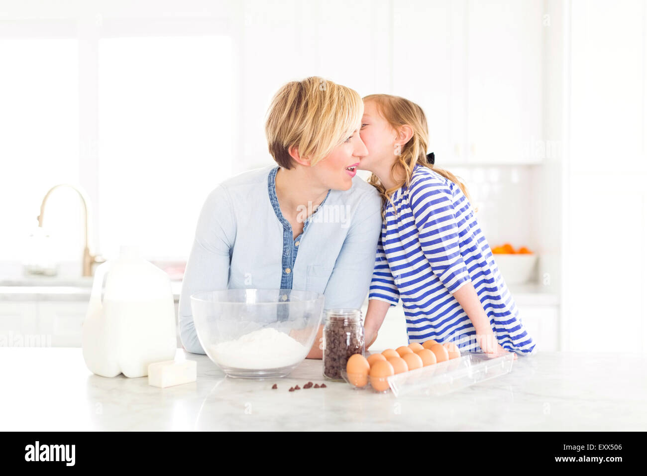 Girl (4-5) whispering into mom's ear - Stock Image