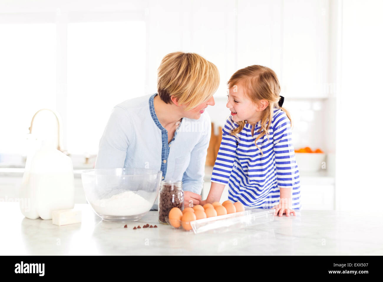 Girl (4-5) talking with mom in kitchen - Stock Image