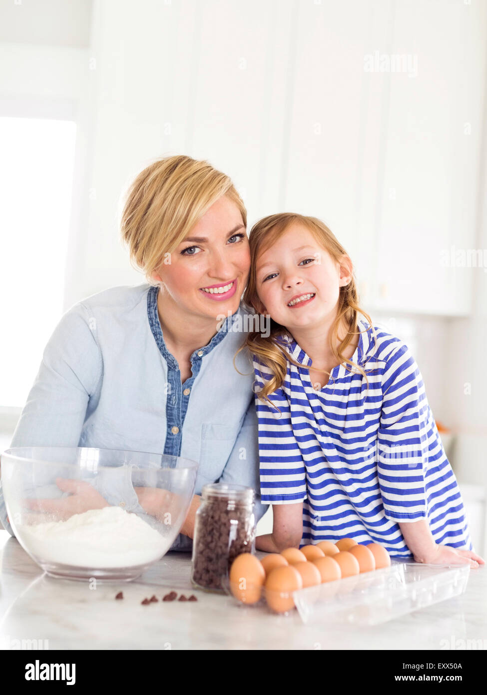 Portrait of girl (4-5) spending time with mom in kitchen Stock Photo