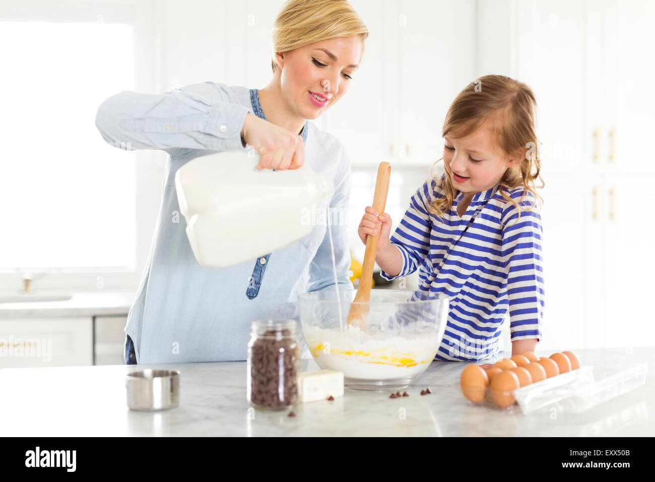 Mother and daughter (4-5) baking - Stock Image