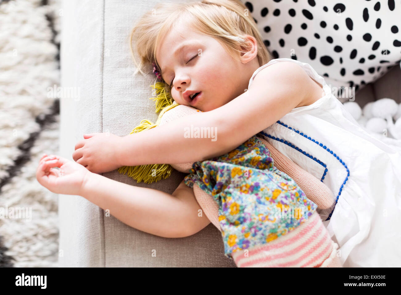 Girl (2-3) napping on sofa - Stock Image