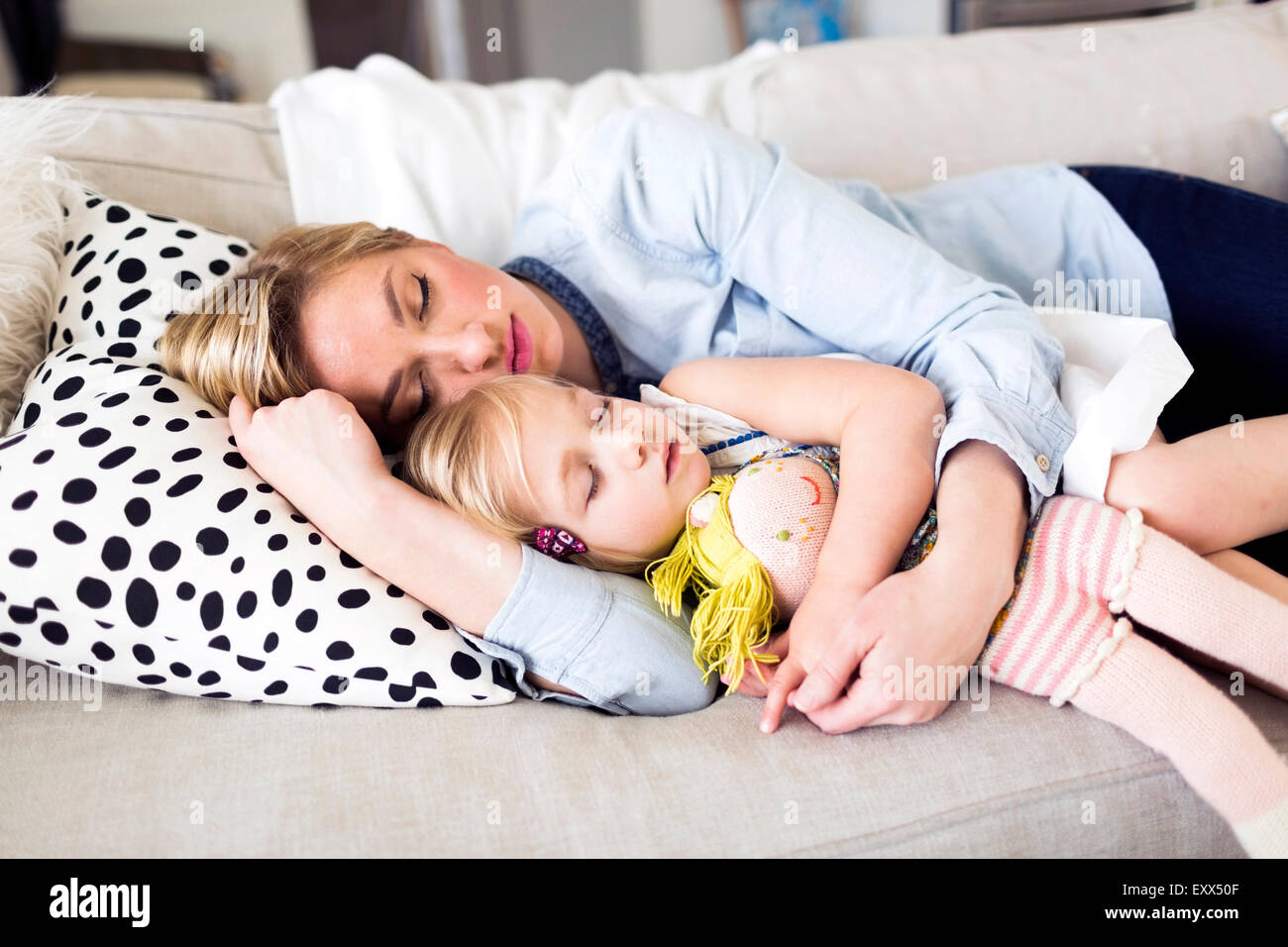 Mother and daughter (2-3) sleeping on sofa - Stock Image