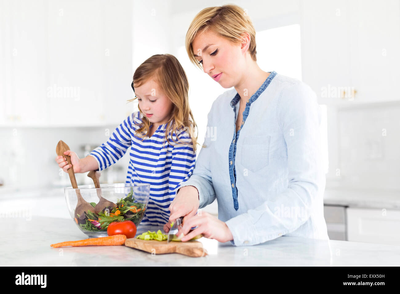 Mother and daughter (4-5) preparing salad - Stock Image