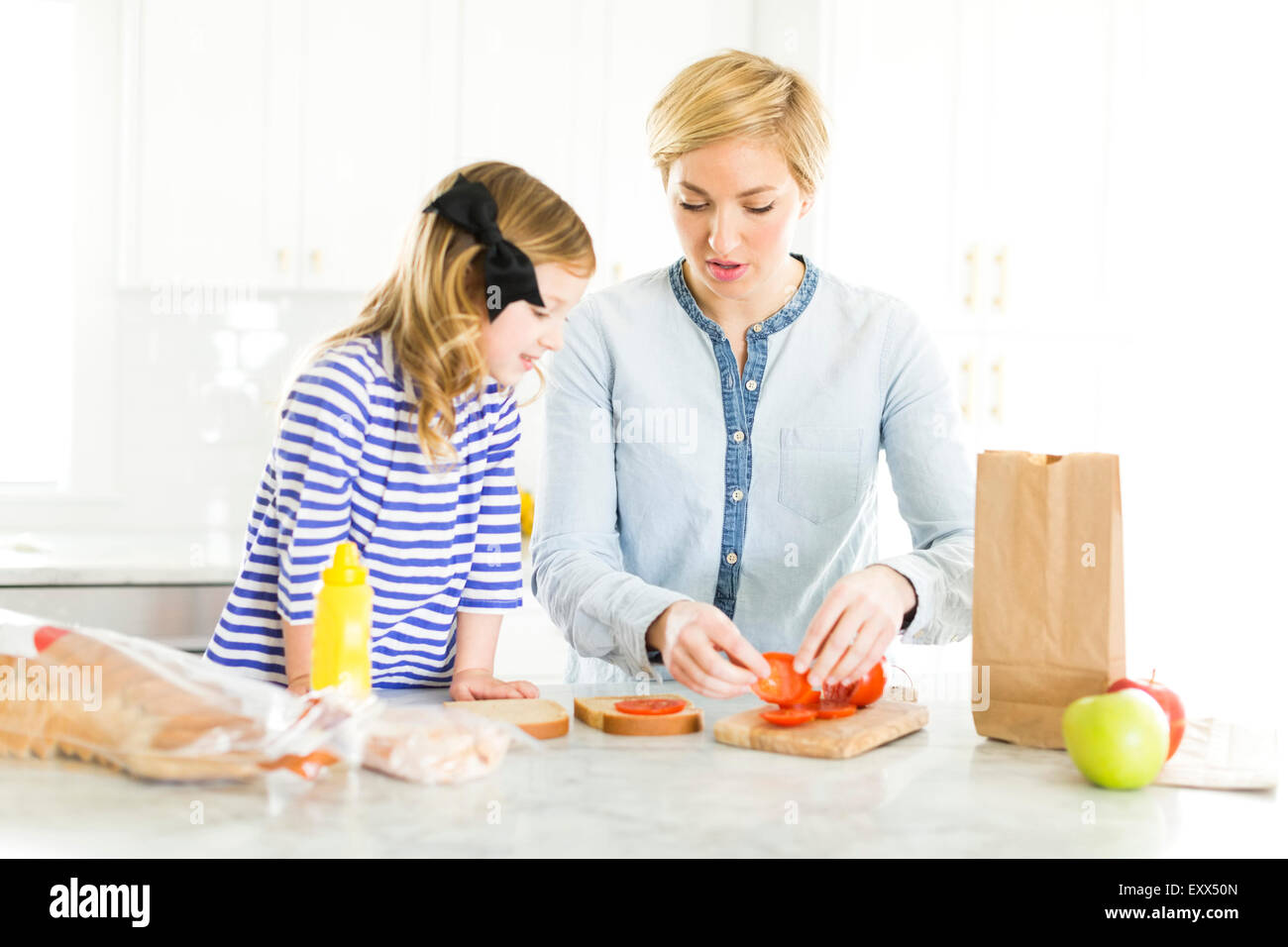 Mother making sandwiches for her daughter (4-5) - Stock Image