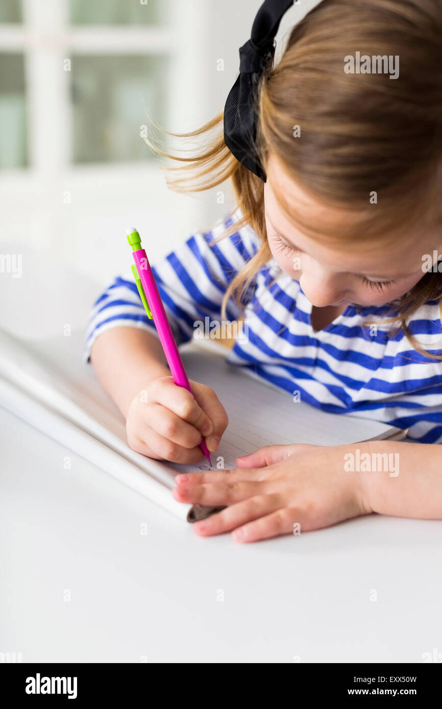 Girl (4-5) drawing in living room - Stock Image