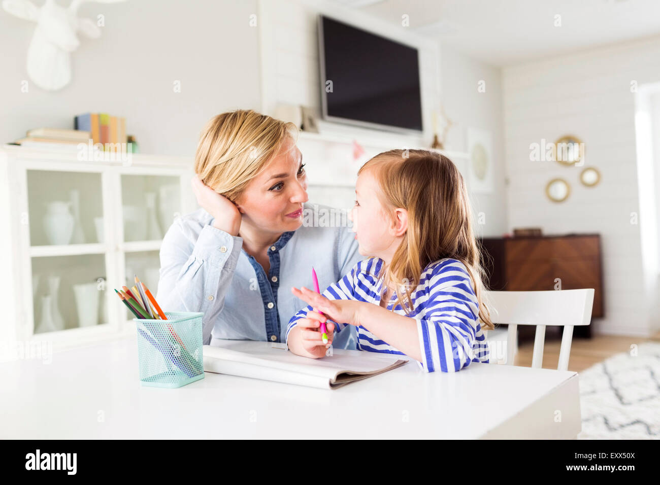 Girl (4-5) drawing with her mom - Stock Image