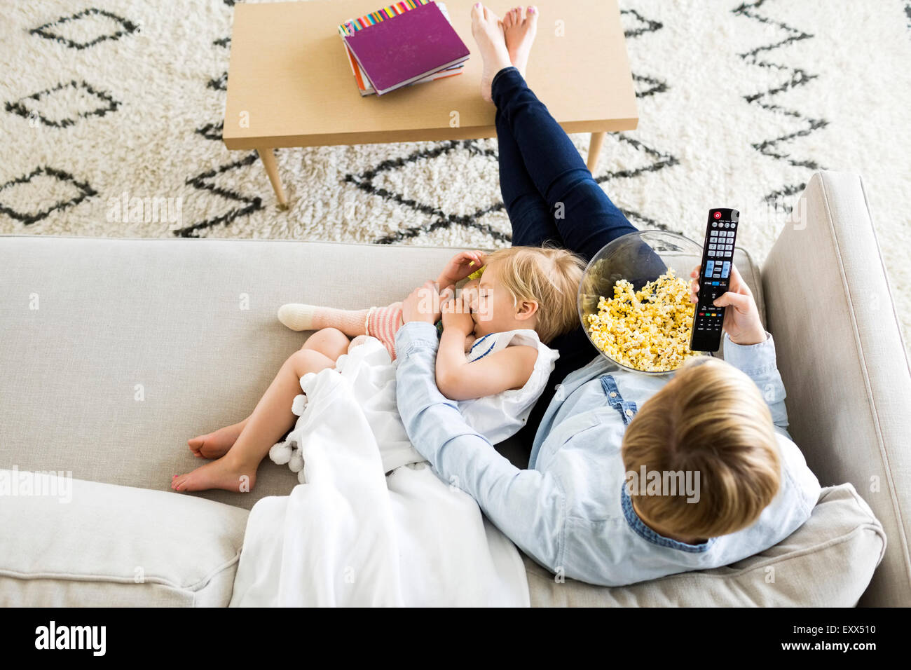 Girl (2-3) sleeping on mom's lap - Stock Image