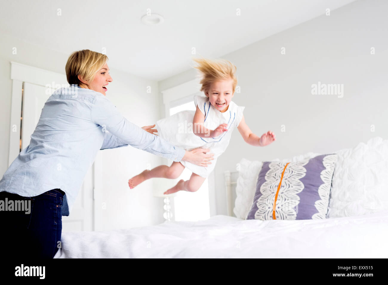 Woman playing with girl (2-3) in bedroom - Stock Image