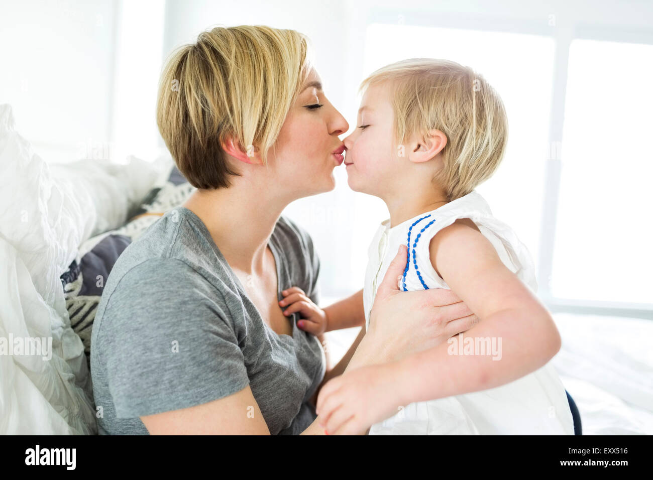 Woman kissing girl (2-3) in bedroom Stock Photo