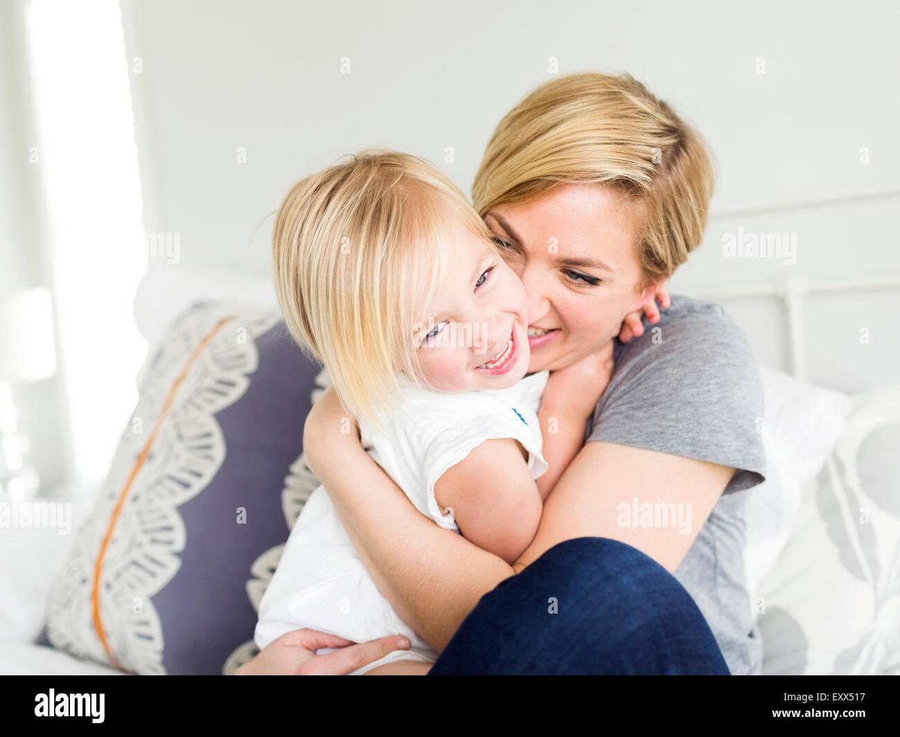Woman hugging daughter (2-3) in bedroom - Stock Image
