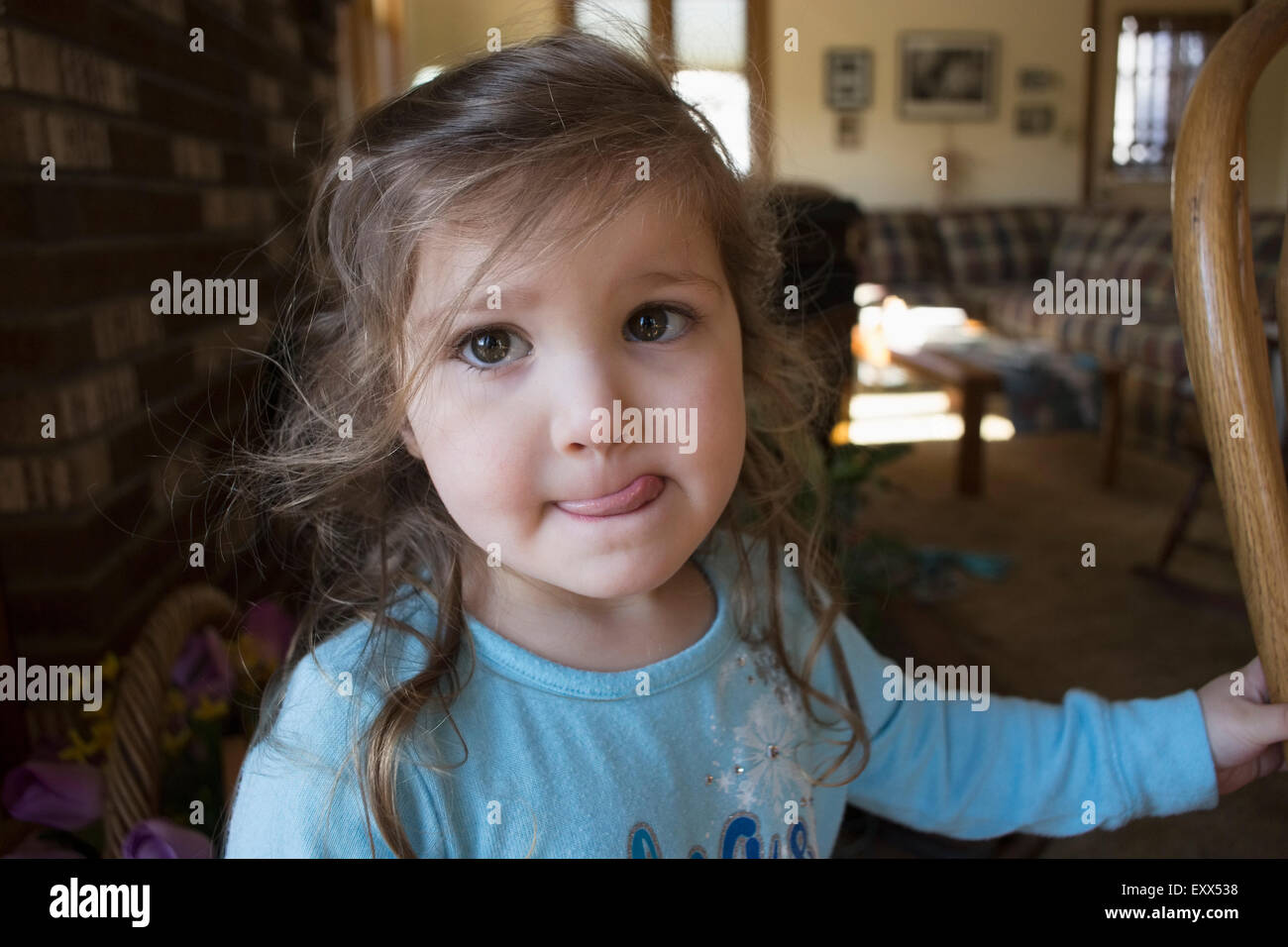 Portrait of girl sticking out tongue - Stock Image
