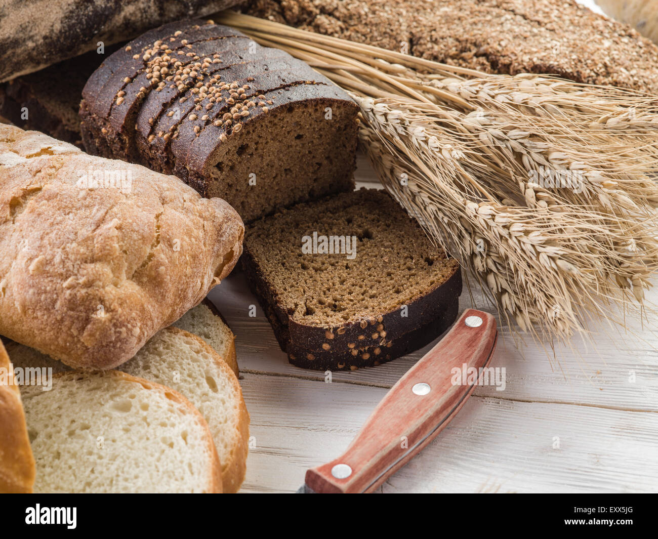 The bread and a wheat on the wooden desk. - Stock Image