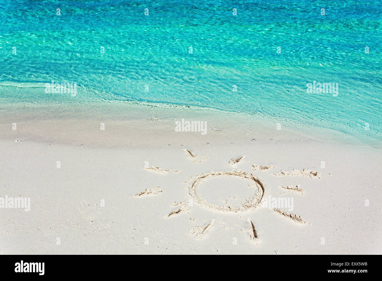 An image of a sun in the sand on the tropical beach - Stock Image