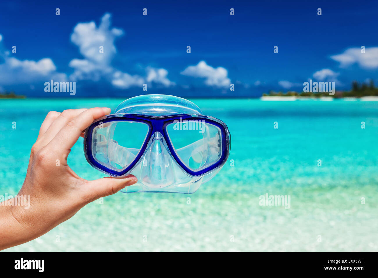Hand holding snorkel googles against blurred beach and blue sky - Stock Image