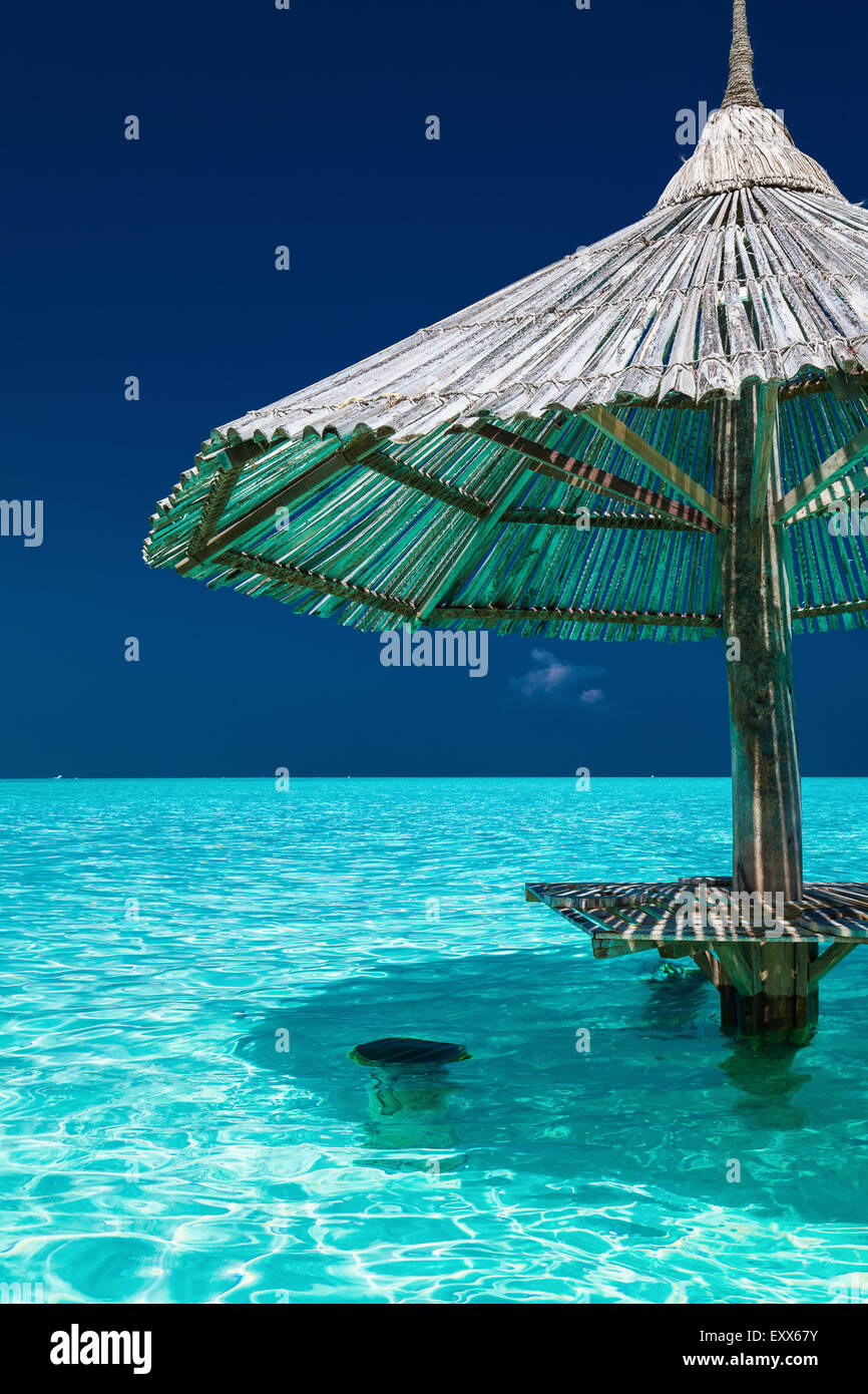 Bamboo beach umbrella with bar seats in the water of tropical island - Stock Image