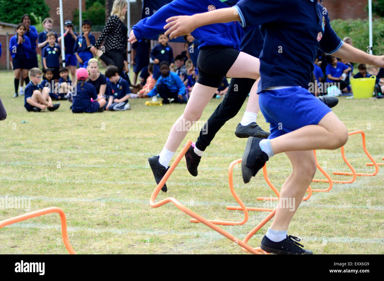 The hurdles race at a primary school sports day. - Stock Image