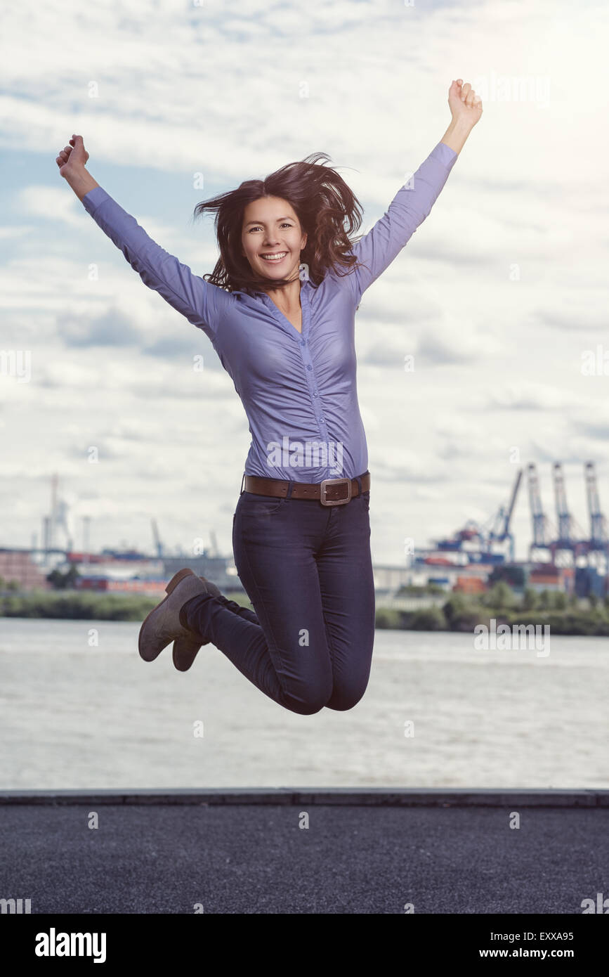 Young woman leaping and cheering for joy with her arms raised and a triumphant smile of glee against a waterway - Stock Image