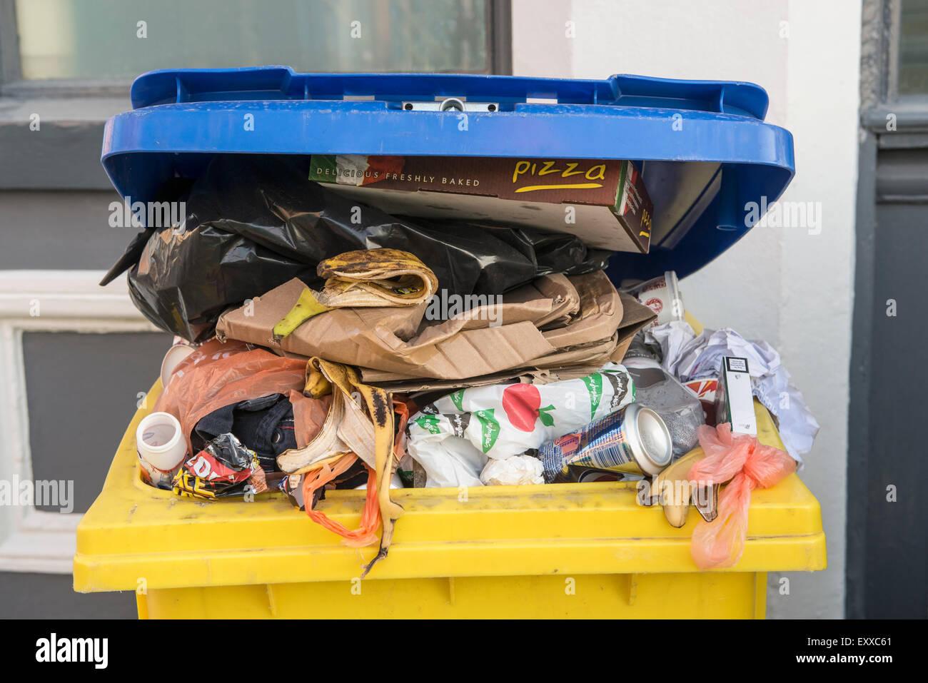 Wheelie bin full of trash / rubbish, Europe - Stock Image