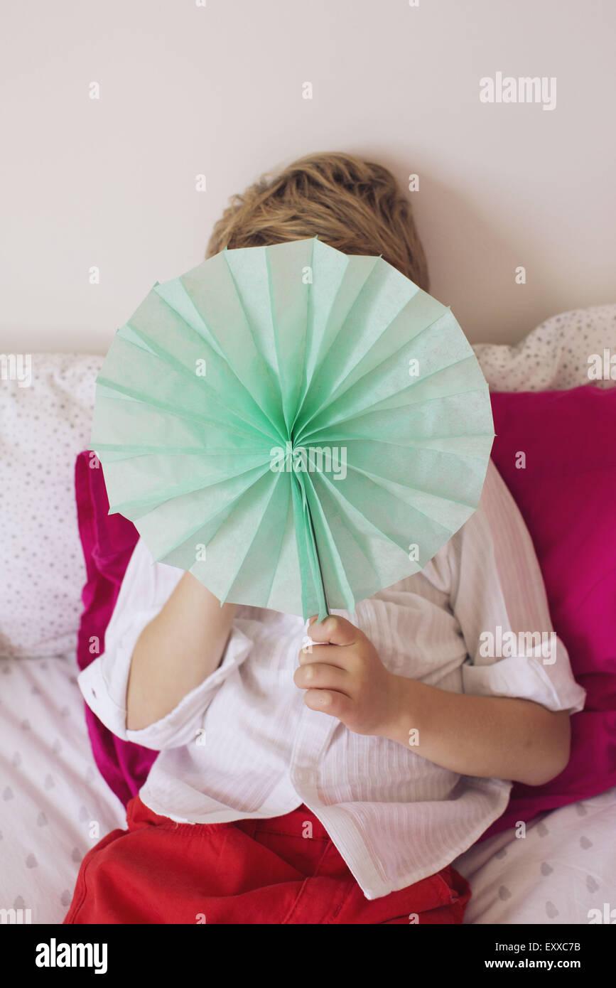 Little boy hiding behind tissue paper flower - Stock Image