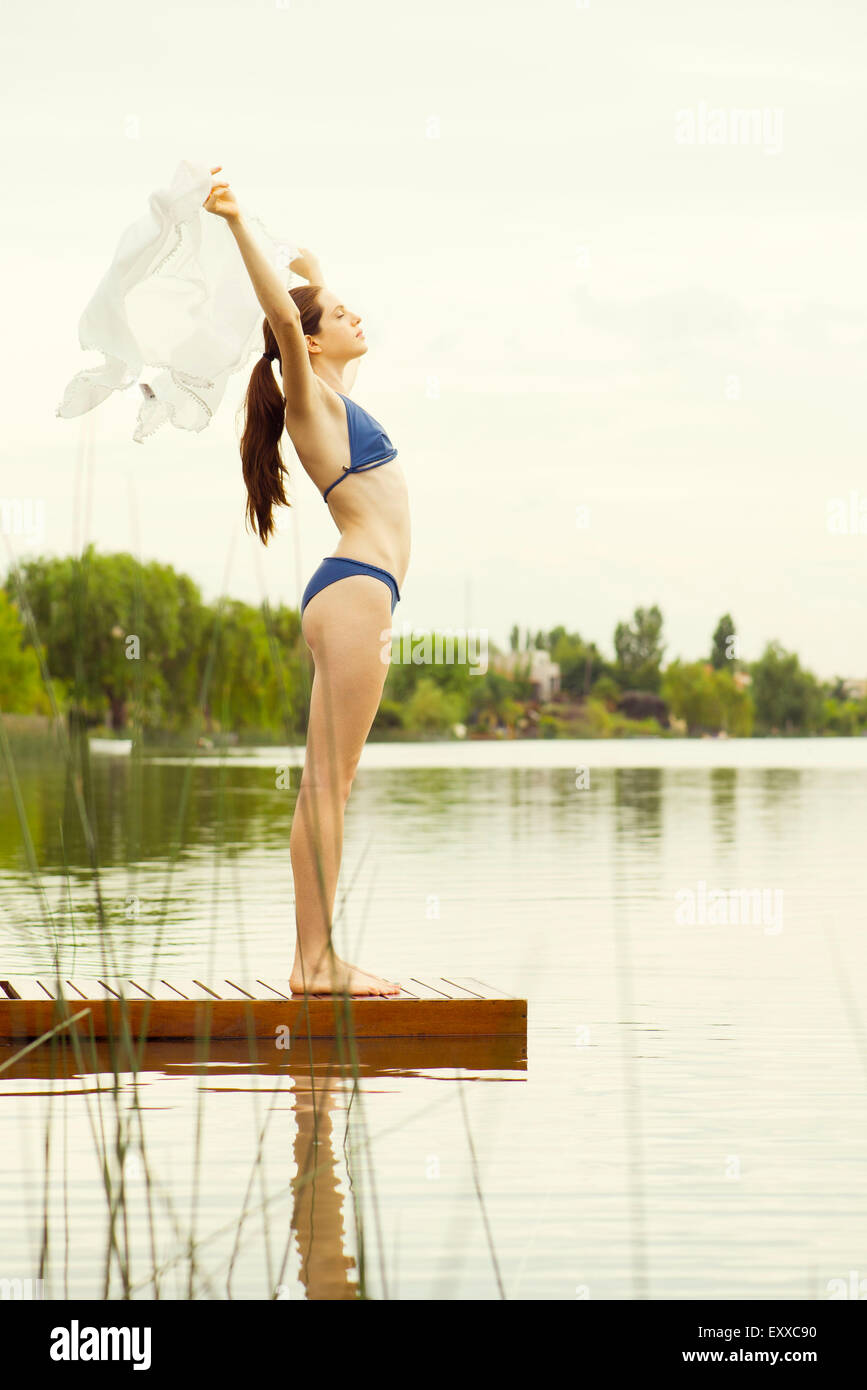 Woman in bikini standing at end of lake pier, holding scarf in the breeze - Stock Image
