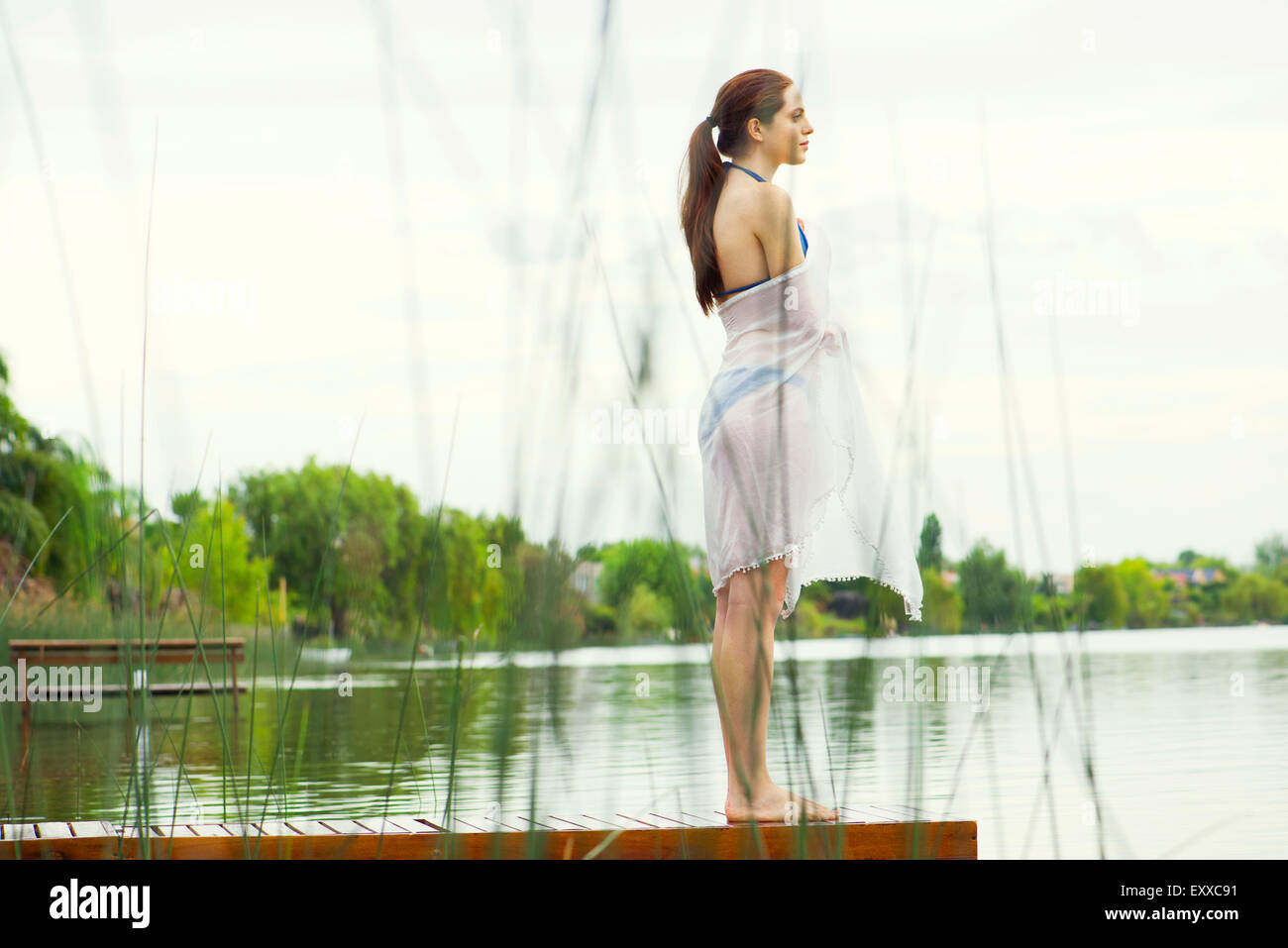 Woman standing at end of lake pier enjoying view - Stock Image