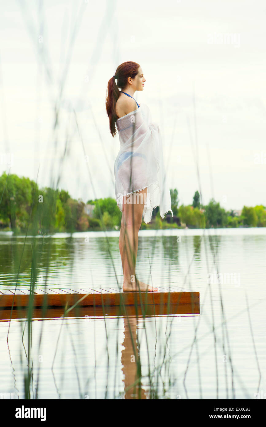 Woman standing at end of lake pier, looking at view - Stock Image
