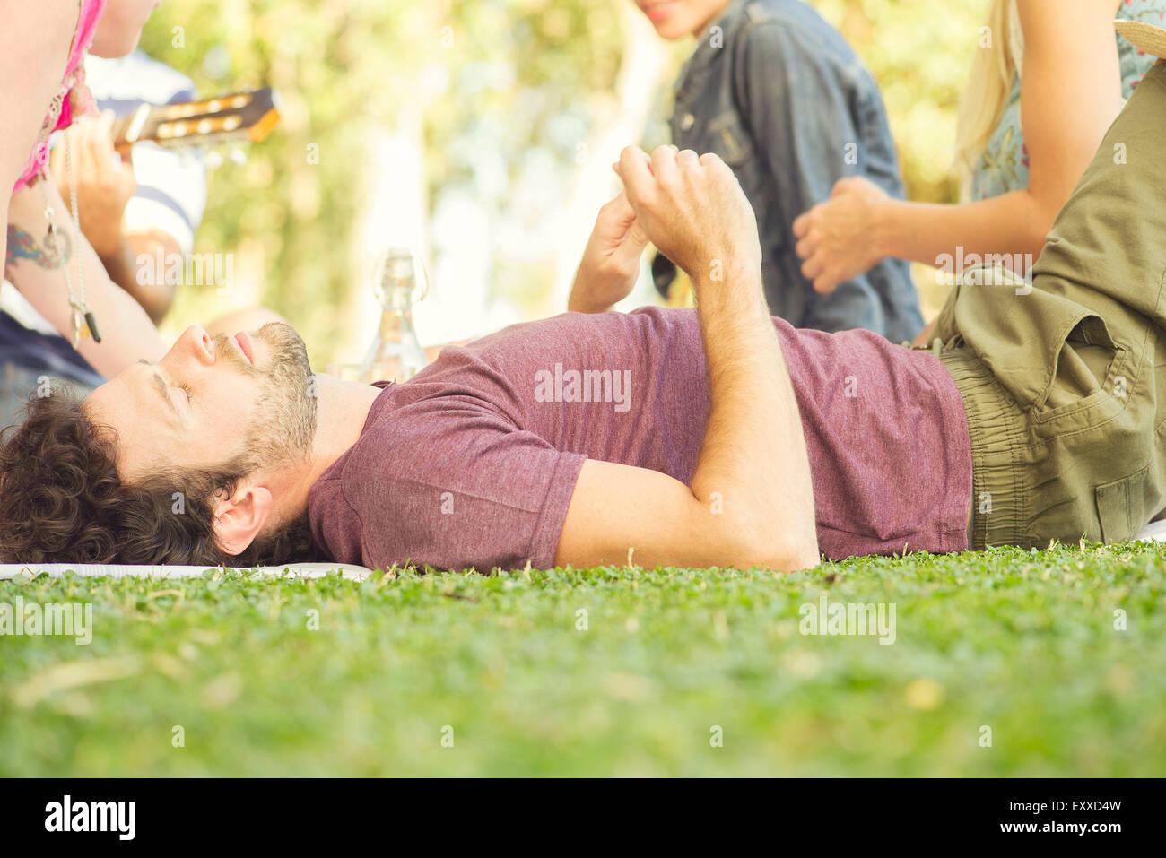Man napping at picnic - Stock Image