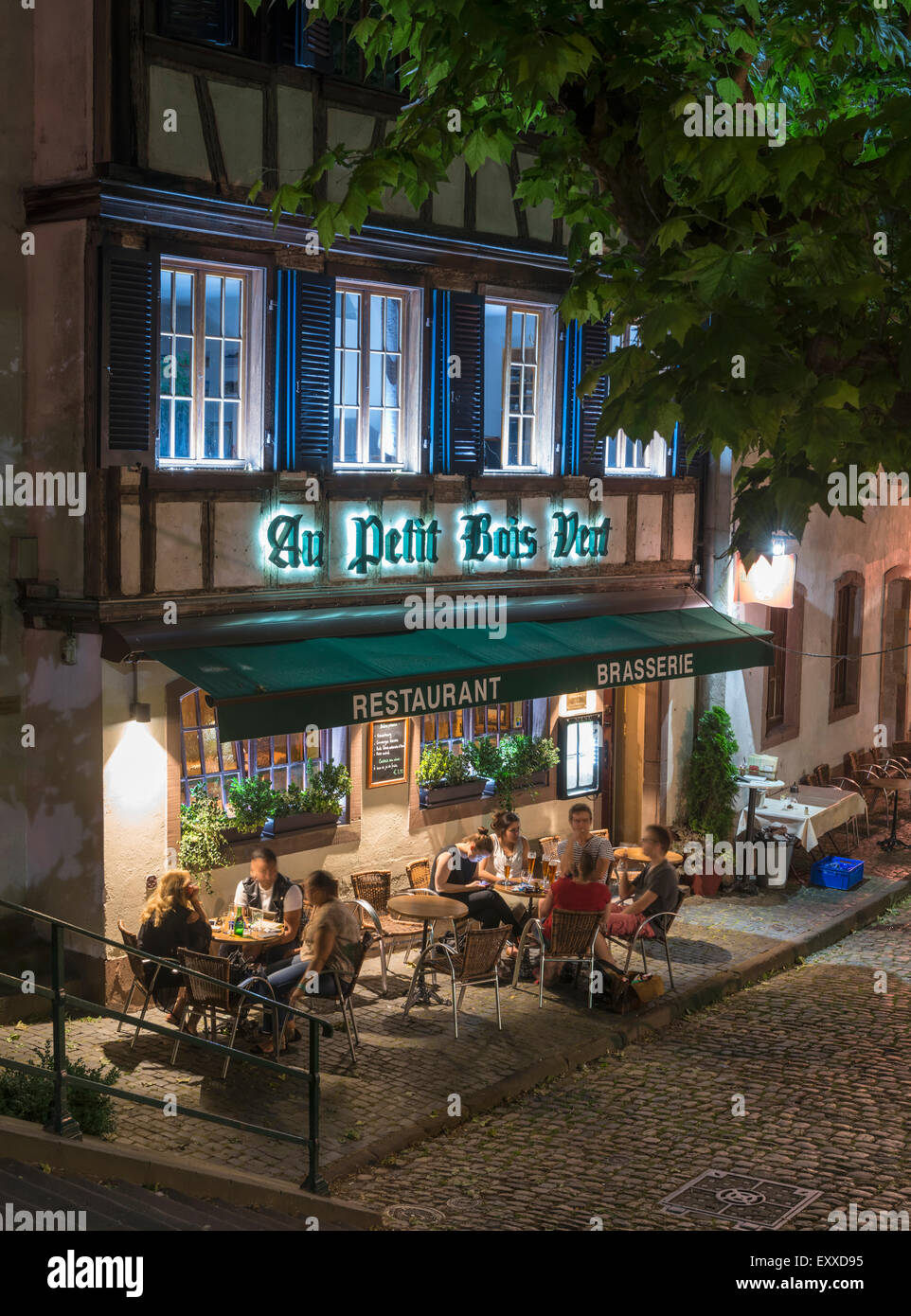 Tourists enjoying an evening drink at a cafe bar restaurant in Petite France old town district, Strasbourg, France, - Stock Image