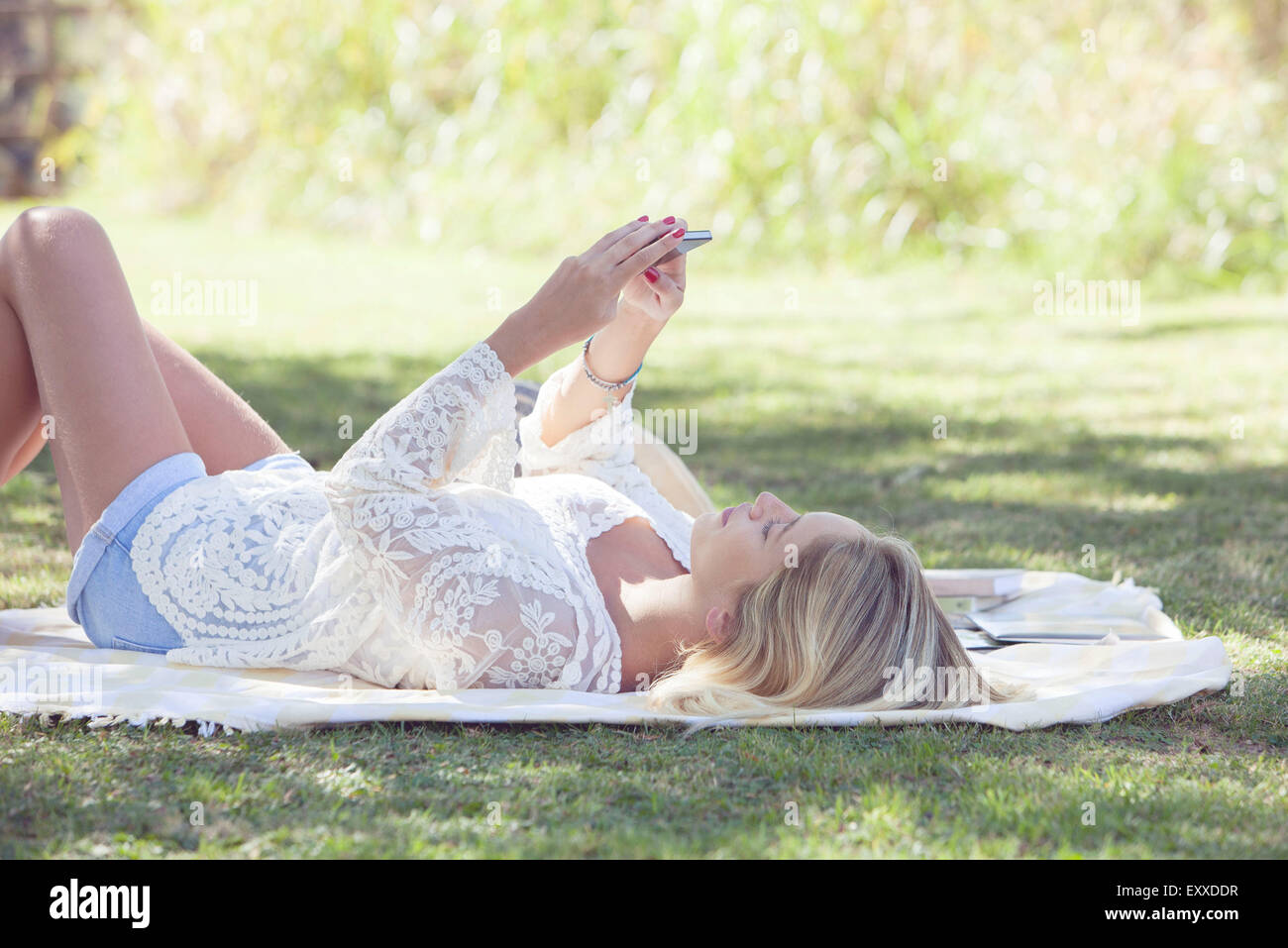 Woman streaming online video content on smartphone outdoors - Stock Image