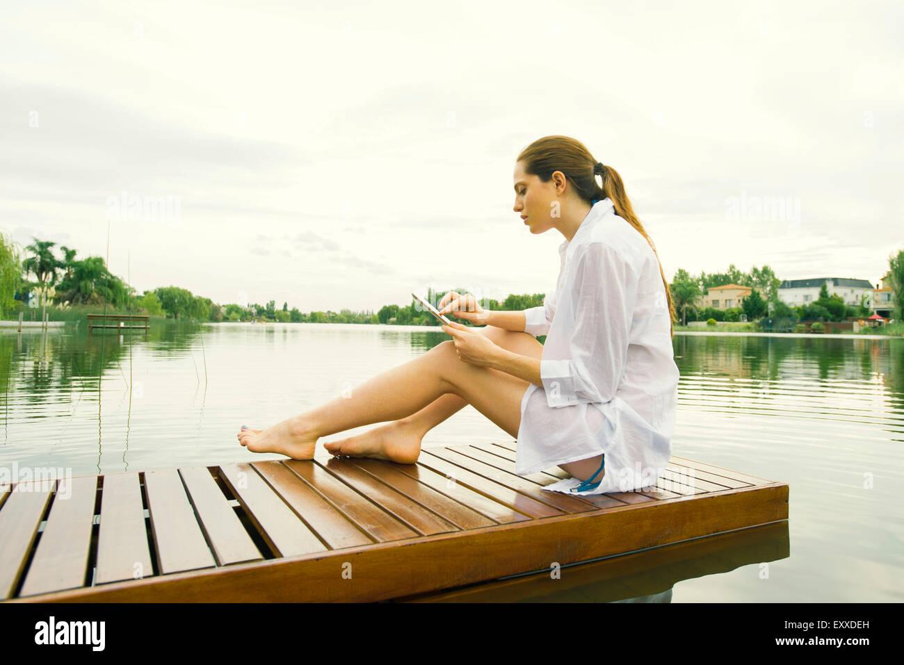 Woman relaxing on lake dock using digital tablet - Stock Image