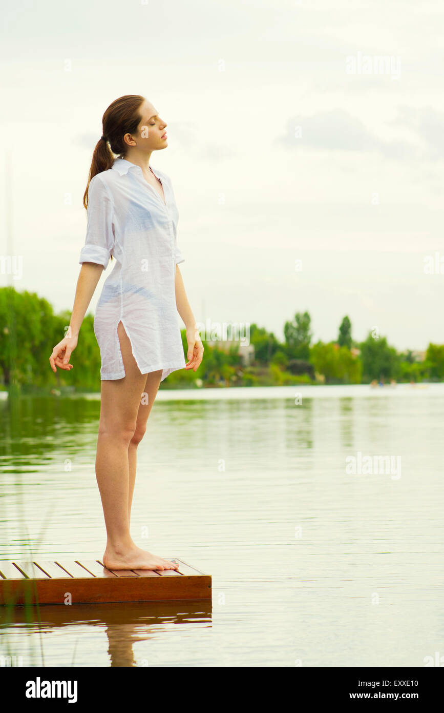 Woman standing at edge of lake dock with eyes closed - Stock Image