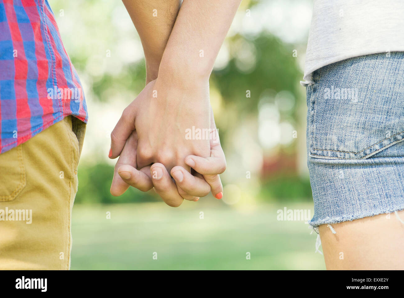 Couple holding hands outdoors, cropped rear view - Stock Image