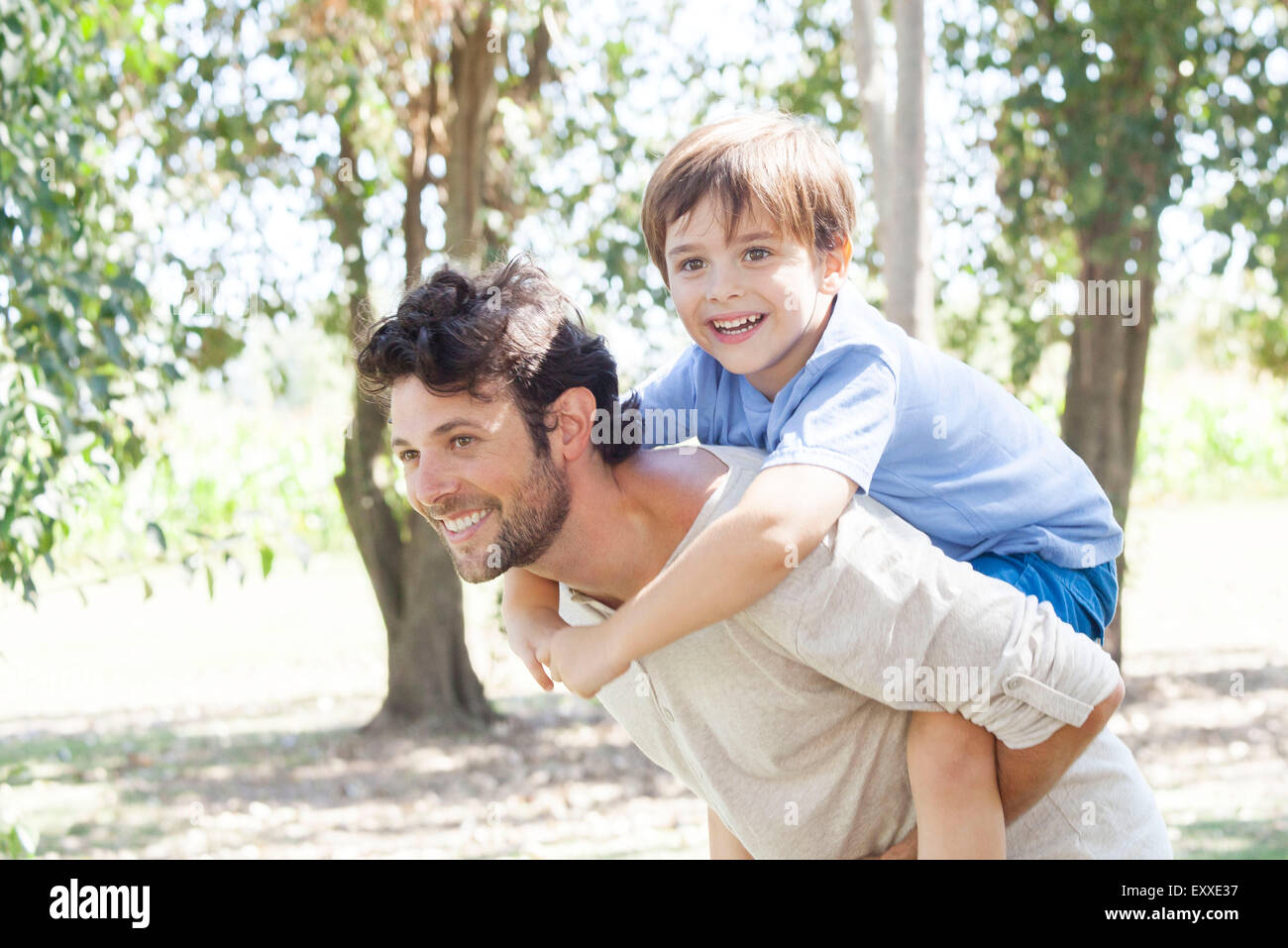 Father carrying young son piggyback - Stock Image