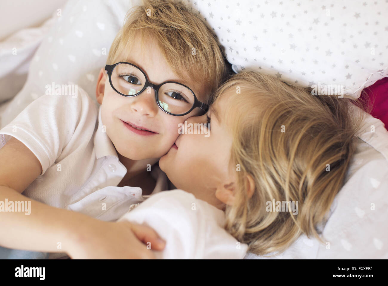 Little girl kissing big brother - Stock Image