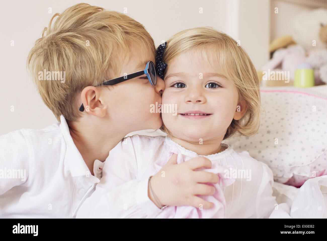 Boy kissing sister's cheek Stock Photo
