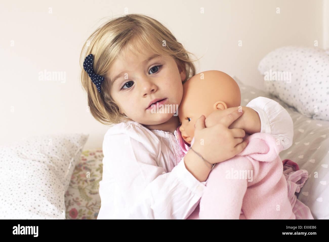 Little girl hugging doll - Stock Image