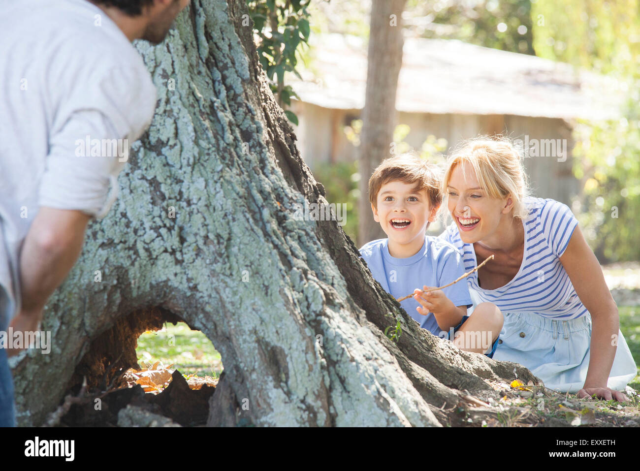 Young boy and mother hiding behind tree, playing hide-and-seek - Stock Image