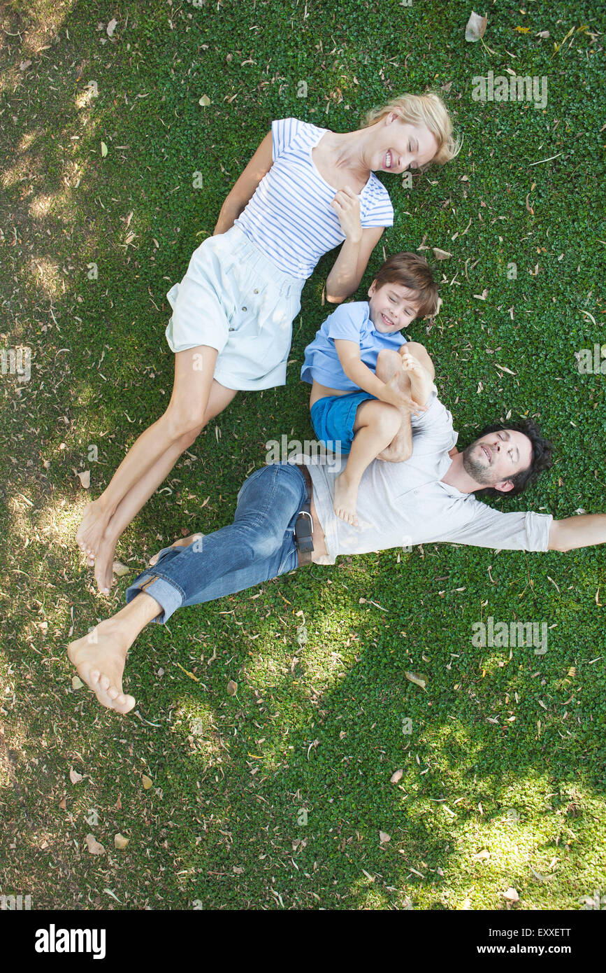 Young family with boy lying together on grass - Stock Image