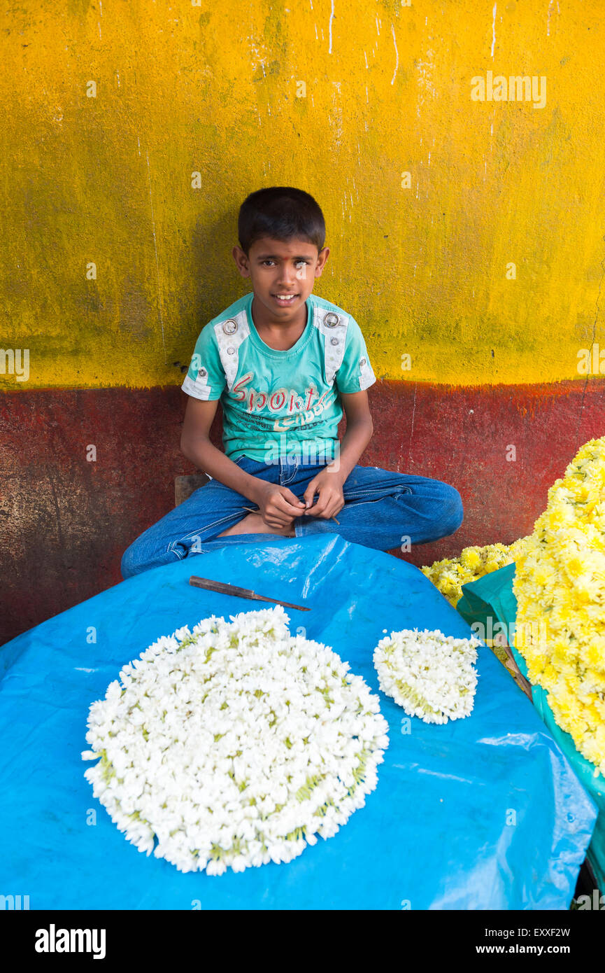 MUMBAI, INDIA - OCTOBER 26, 2012: Indian child helps string flower decorations for the upcoming Hindu Diwali festival. - Stock Image