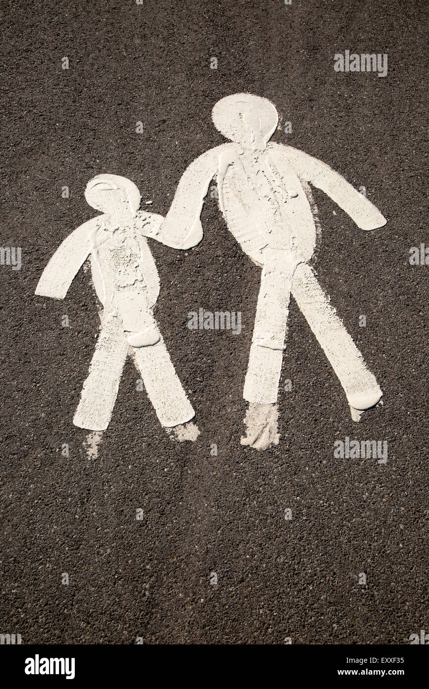 Child and parent figures holding hands on tarmac pavement, Mumbles, South Wales, UK - Stock Image