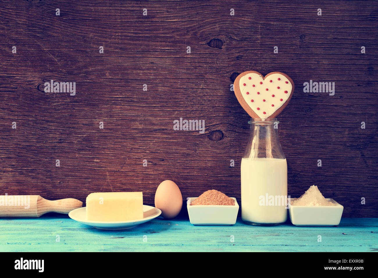 a heart-shaped cookie and the ingredients for cook it, such as milk, eggs, flour, butter and sugar on a blue rustic - Stock Image