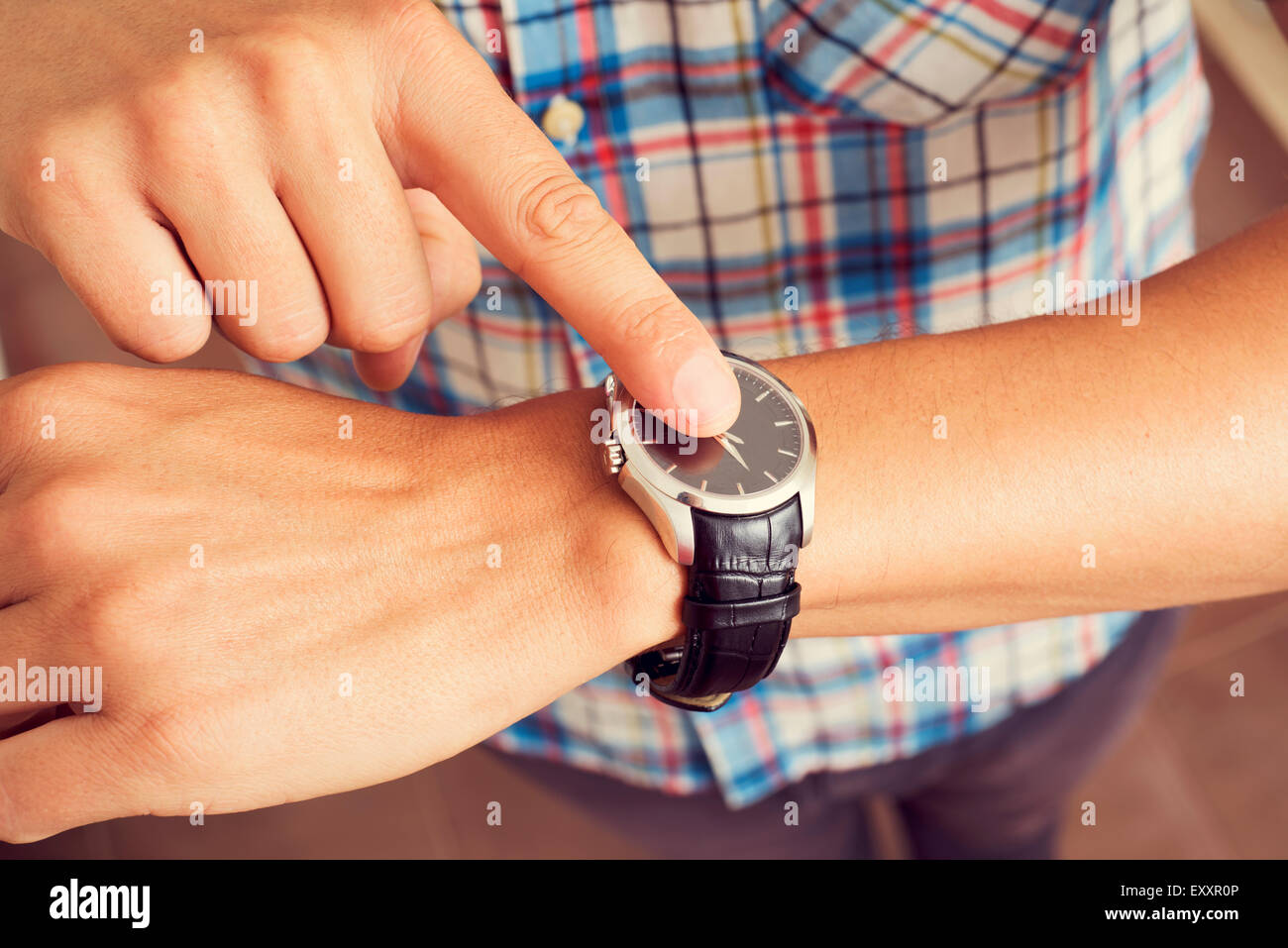 closeup of a young caucasian man tapping his forefinger on his wristwatch - Stock Image