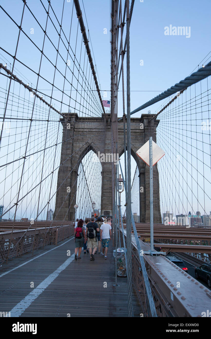 NEW YORK - May 30, 2015: People walking across the Brooklyn Bridge in New York city. Completed in 1883, it connects - Stock Image