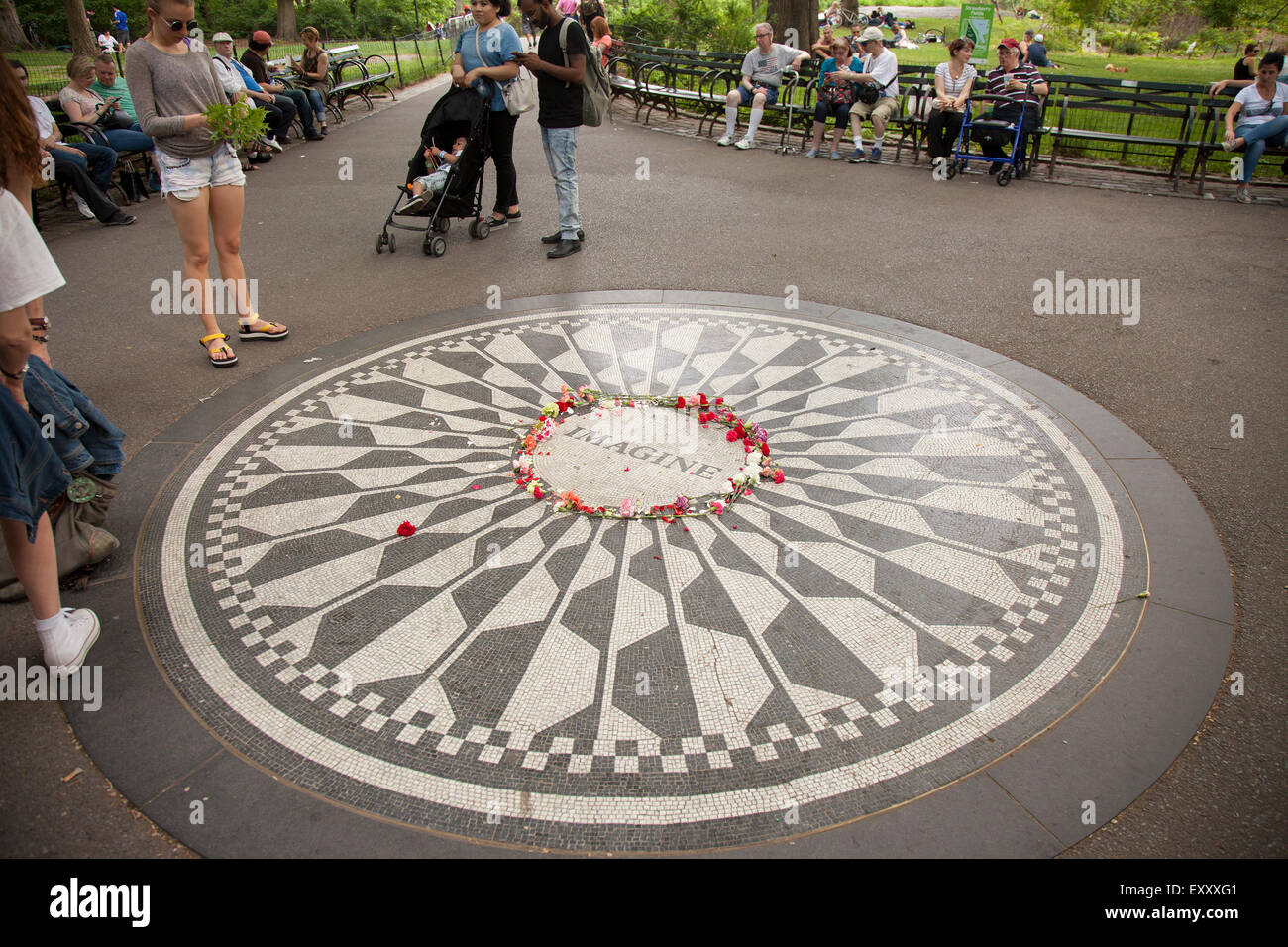 NEW YORK - May 25, 2015: People gather at Strawberry Fields in Central Park, New York City. Strawberry Fields is Stock Photo