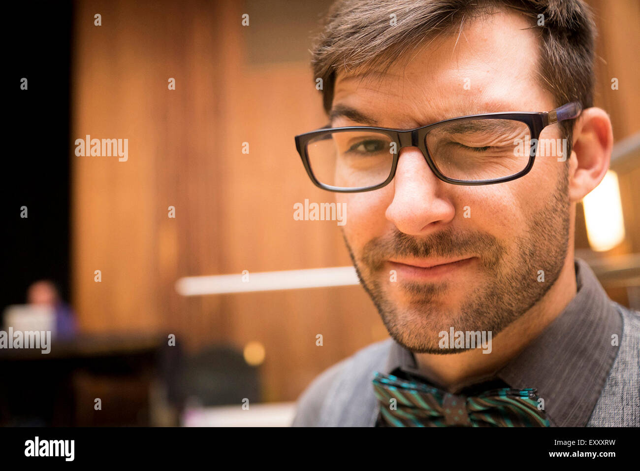 Man dressed up wearing a bow tie and wearing a peculiar expression - Stock Image